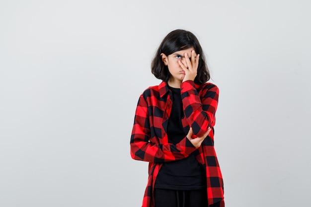 Ragazza teenager che guarda attraverso le dita in camicia casual e che sembra annoiata, vista frontale.