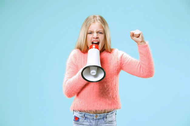 青いスタジオでメガホンで発表する10代の少女
