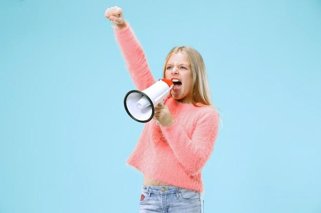 Девушка-подросток делает объявление с мегафоном в голубой студии