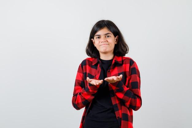 Ragazza teenager che fa o riceve un gesto in t-shirt, camicia a scacchi e sembra soddisfatta, vista frontale.