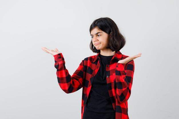 10代の少女は、tシャツ、市松模様のシャツで体重計のジェスチャーを作成し、物思いにふける、正面図を探しています。