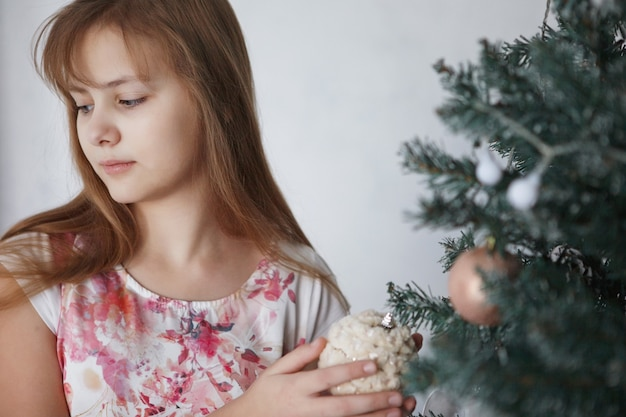 Teen girl near a christmas tree. a teenager with long hair in a colorful dress decorates new year's toys.