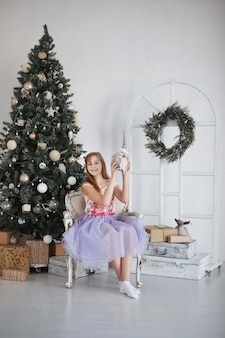 Teen girl near a christmas tree. teenager with long hair in a colorful dress sits in an armchair against the backdrop of a festive decoration.