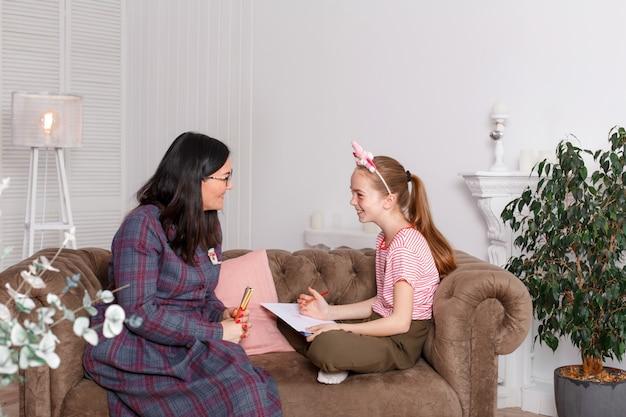 Девочка-подросток на приеме у психотерапевта. сеанс психотерапии для детей. психолог работает с пациентом. девушка рисует карандашом на бумаге вместе с врачом