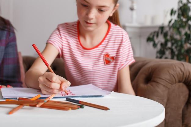 心理療法士のレセプションで十代の少女。子供のための心理療法セッション。心理学者は患者と協力します。女の子は医者と一緒に紙に鉛筆で鉛筆を描画します