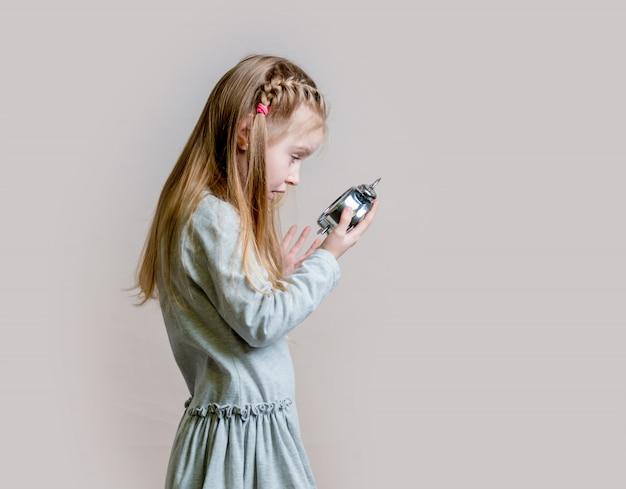 Teen girl in pajamas with alarm cloock