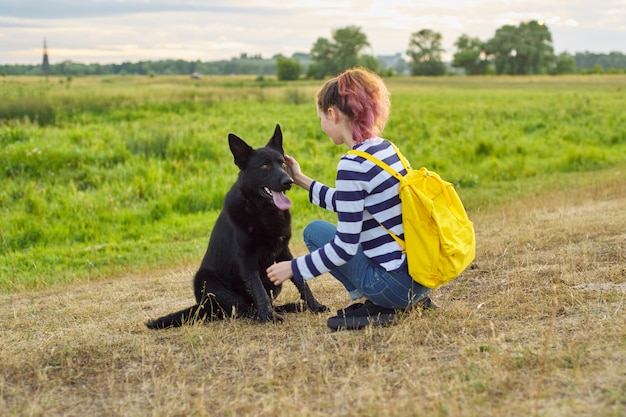 Teen girl pet owner playing and talking with big black shepherd dog