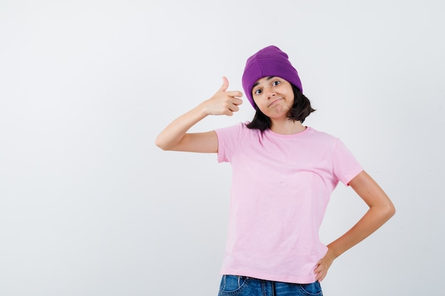 Teen girl in pink t-shirt, beanie, jeans showing thumb up, holding hand on waist and looking cheerful , front view.