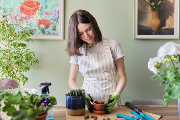Девочка-подросток сажает в горшок небольшой кактус. хобби и отдых, домашнее садоводство, комнатное растение, городские джунгли в квартире, концепция друзей в горшках