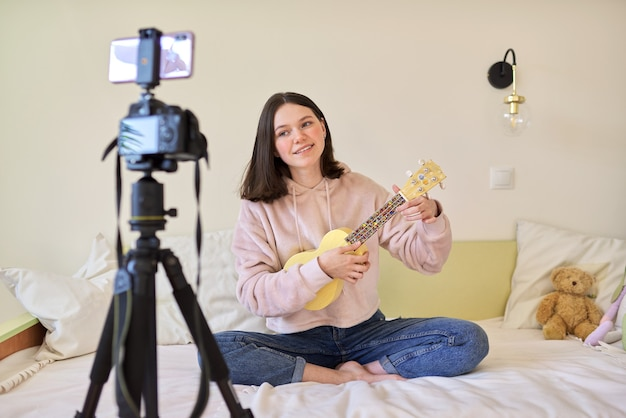 Teen girl playing on ukulele. blog, music channel, vlog, girl studying online, talking to followers and playing music