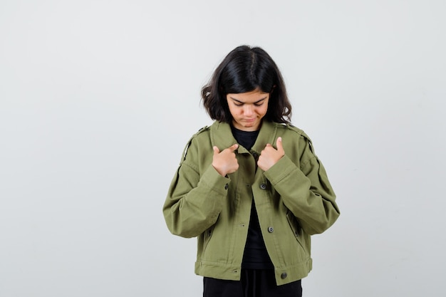 10대 소녀는 군대 녹색 재킷을 입고 자신을 가리키며 실망한 표정을 짓고 있습니다.
