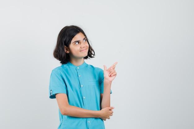 青いシャツを着て、満足そうに見える十代の少女。