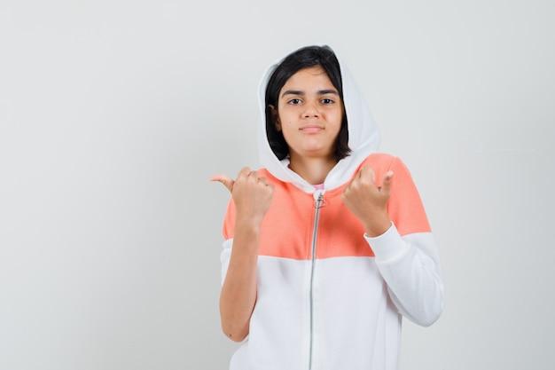 Ragazza teenager che indica ai lati differenti in rivestimento e che osserva perplesso.