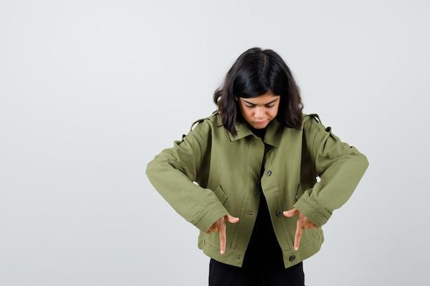 Девушка-подросток указывая вниз в зеленой куртке армии и смотрящая сосредоточенная. передний план.