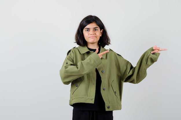 Ragazza teenager che punta a destra in giacca verde militare e sembra allegra, vista frontale.
