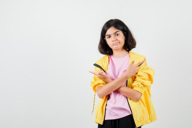 Tシャツ、ジャケット、物思いにふけるように交差した手で反対方向を指している十代の少女。正面図。