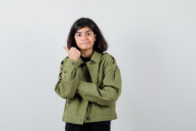 Девушка-подросток указывает на левую сторону большим пальцем в футболке, зеленой куртке и смотрит осторожно. передний план.