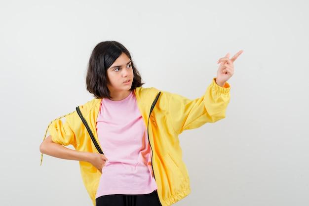 指で上向き、黄色のトラックスーツ、tシャツ、物思いにふける、正面図で腰に手を保持している10代の少女。