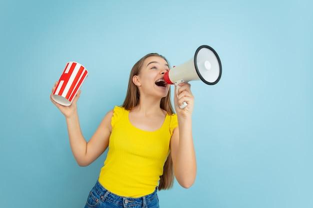Портрет девушки-подростка с мегафоном и бумажным стаканчиком, изолированным на синей стене