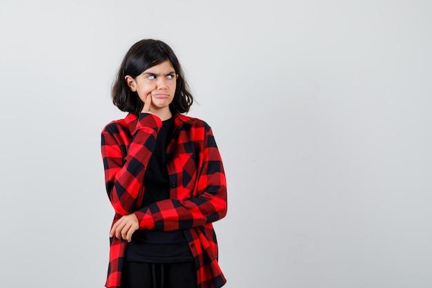 カジュアルなシャツのディンプルに指を押して物思いにふける十代の少女。正面図。