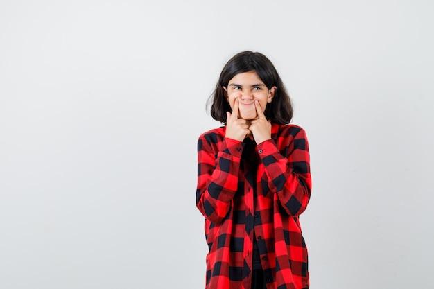 Девушка-подросток нажимает пальцами на ямочки на щеках, смотрит в сторону в повседневной рубашке и с любопытством смотрит. передний план.