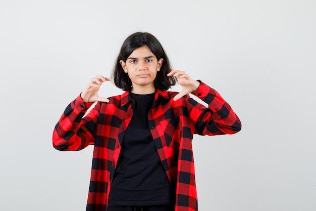 Ragazza teenager che finge di prendere qualcosa in maglietta, camicia a scacchi e guarda attenta. vista frontale.