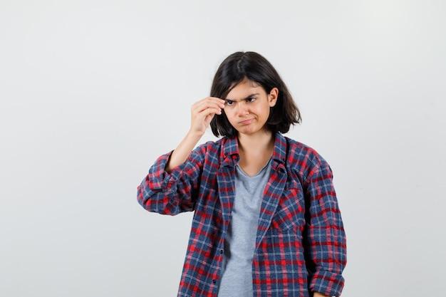 Ragazza teenager che finge di tenere qualcosa di minuscolo in abiti casual e sembra concentrata, vista frontale.