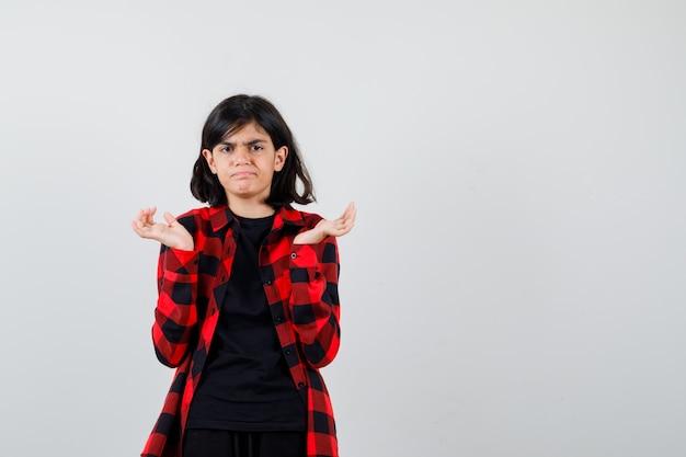 Tシャツ、市松模様のシャツで手を脇に上げて、失望しているように見える10代の少女、正面図。