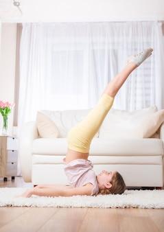 部屋で彼女の足を上げる十代の少女