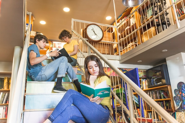 Teen girl reading book on steps near classmates