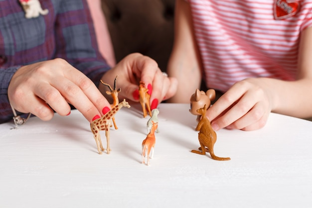 Teen girl on reception at the psychotherapist. psychotherapy session for children. the psychologist works with the patient. the girl plays toy animals together with a doctor therapist