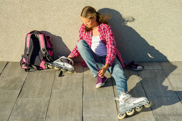 Teen girl removes sneakers and clothes roller skates