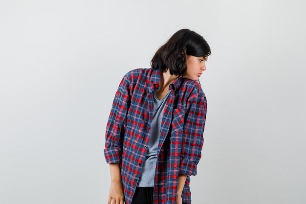 Ragazza teenager che riposa il mento sulla spalla in camicia a scacchi e guarda premurosa, vista frontale.