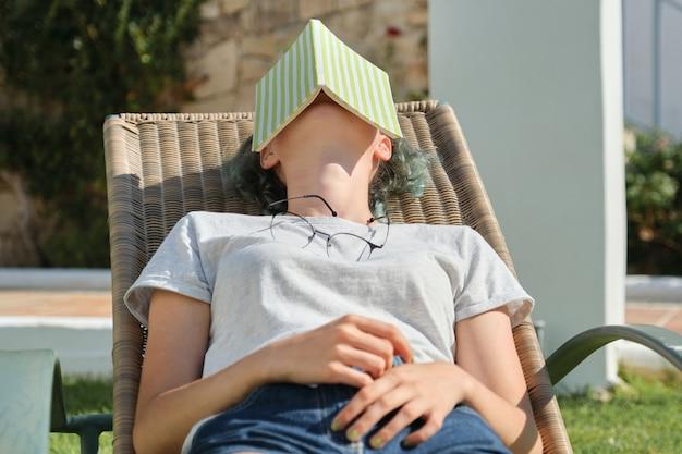 緑の芝生の椅子に座って屋外で休んでいる十代の少女