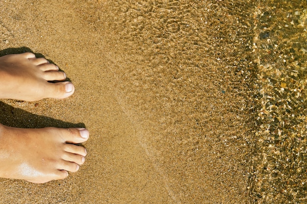 Босые ноги девушки-подростка, стоящие на песке пляжа озера у воды на летних каникулах. концепция отдыха на пляже в летнюю жару
