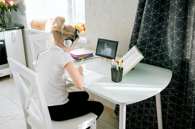 Teen girl school pupil wears headphones conference calling studying online with remote tutor from home. teenage using laptop talking in webcam video chat learning lesson with distance teacher.