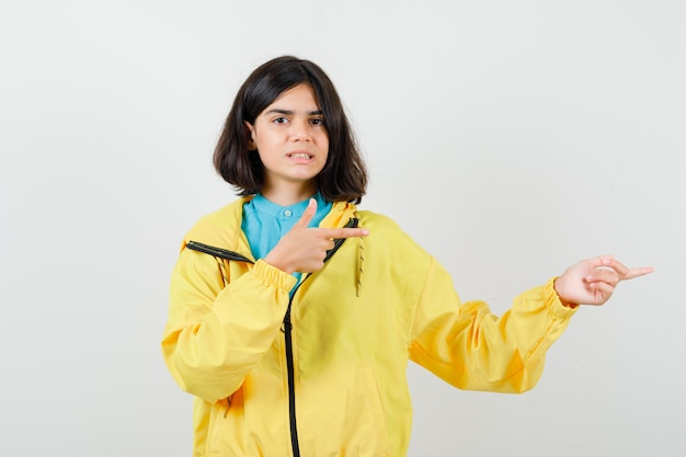 Teen girl in shirt, yellow jacket pointing right and looking cheerless , front view.