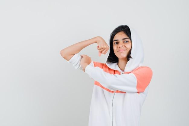 Teen girl showing her arm muscle in sweatshirt and looking satisfied.