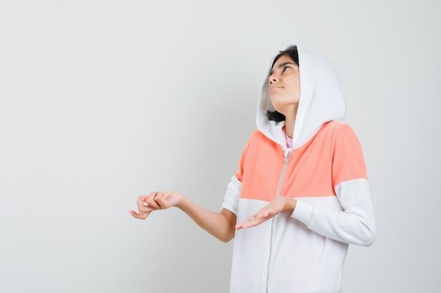 Девушка-подросток показывает жест idk в белой куртке и выглядит беспомощной.