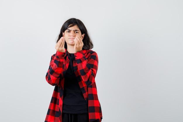Tシャツ、市松模様のシャツでイタリアのジェスチャーを示し、不満を探している10代の少女、正面図。