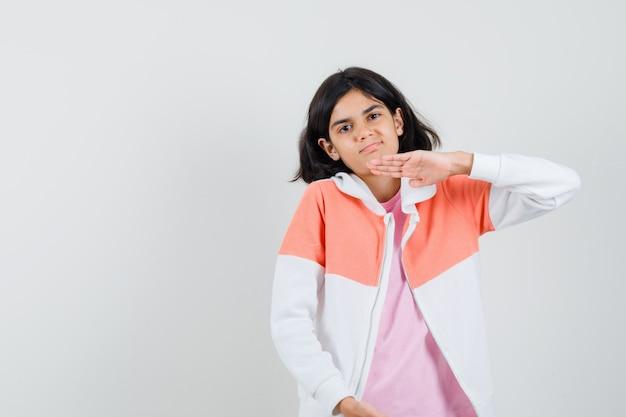 Ragazza teenager che mostra il segno di grandi dimensioni in giacca, camicia rosa e sembra soddisfatta.