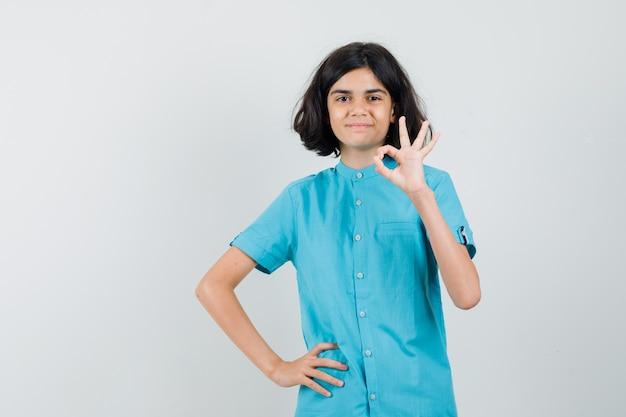 Девушка показывает одобренный жест в голубой рубашке и смотрит рад.