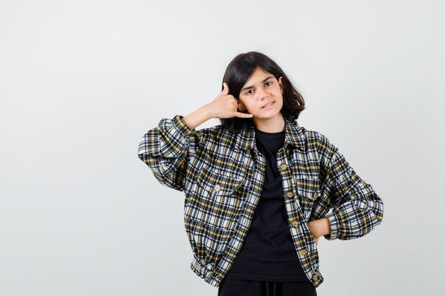 Ragazza teenager che mostra il gesto del telefono in camicia casual e guardando fiducioso, vista frontale.