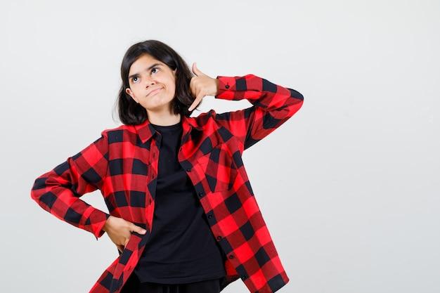10대 소녀는 티셔츠, 체크무늬 셔츠를 입고 무모한 모습을 하고 정면을 바라보며 전화 제스처를 보여줍니다.