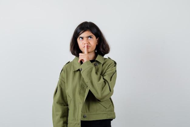 Tシャツ、緑のジャケットで沈黙のジェスチャーを示し、集中して見える十代の少女。正面図。