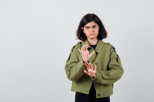 Ragazza teenager che mostra il gesto di arresto in giacca verde militare e sembra cupa. vista frontale.