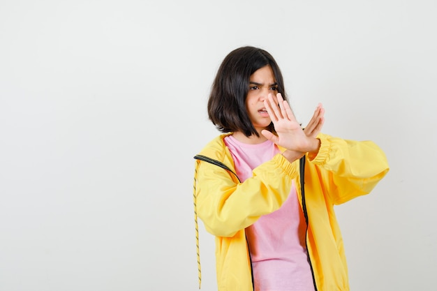 Tシャツ、ジャケットで停止ジェスチャーを示し、イライラしている10代の少女。正面図。