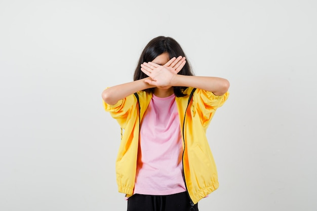 Teen girl showing stop gesture with crossed hands in t-shirt, jacket and looking confident , front view.