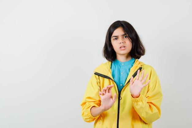 Ragazza teenager che mostra il gesto di arresto in giacca gialla e sembra seria, vista frontale.