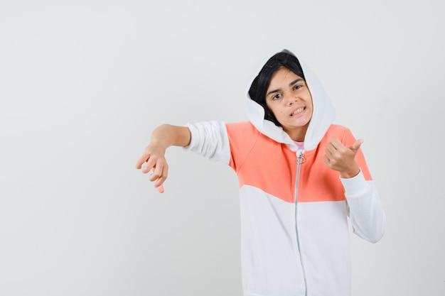 白いジャケットで親指を上下に示し、混乱しているように見える十代の少女。